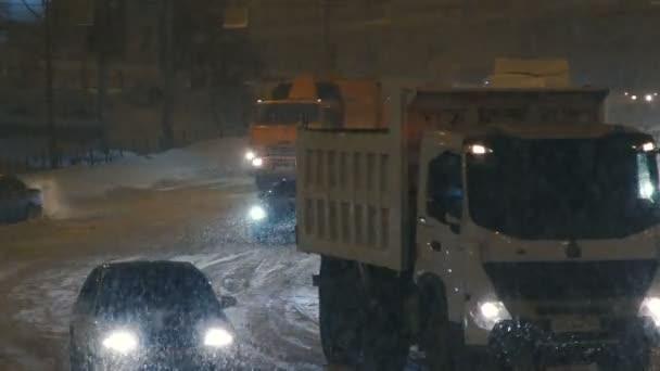 Traktor pro odklízení sněhu, pohybující se na město večer