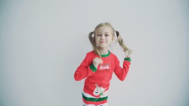 Portréja egy aranyos lány, Pigtailek, pizsamában fehér háttér