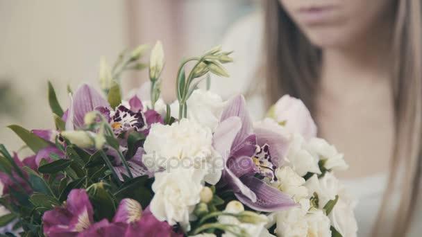 Egy gyönyörű lány virágüzlet teszi egy virág elrendezése. Virág kompozíció