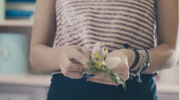 Közeli kép: ágak, növények és egy virág bimbó a kezében a virágárus