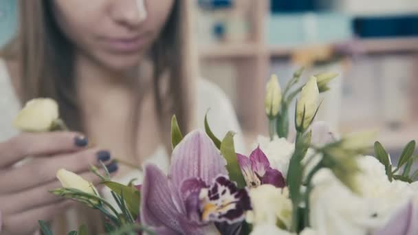 Florist at work: woman making bouquet of different flowers.