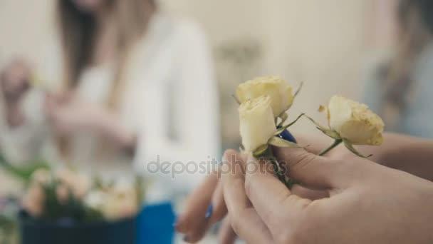 Bílá růže v rukou květinářství. Vytvoření květinové kompozice
