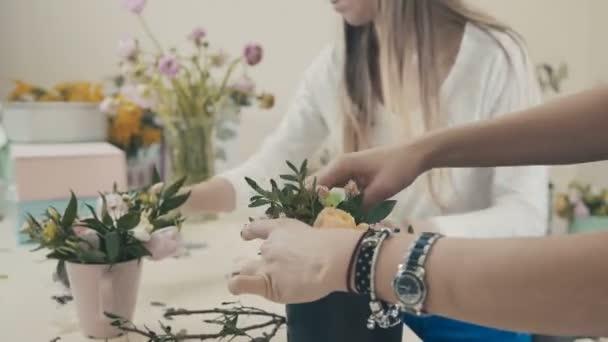 Két virágárus lányok a virág-pult működik. Virágüzlet.