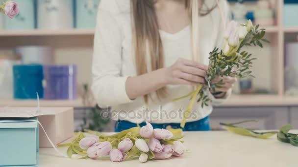 A virágárus lány, a munka teszi egy csokor rózsaszín tulipánok