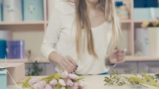 A virágárus, a munka teszi egy csokor rózsaszín tulipánok.