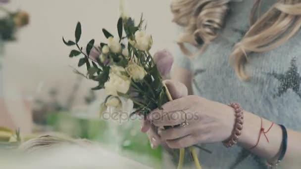 Egy nő virágüzlet teszi egy csokor fehér rózsával. Virágbolt