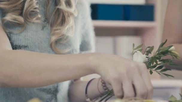 Egy nő virágüzlet teszi egy csokor fehér rózsával