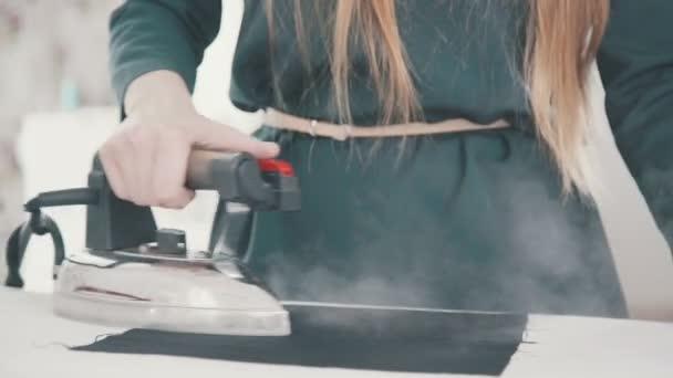 Švadlena žena par kousek zelené látky pomocí žehličky