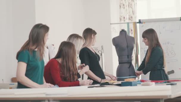 Жінка приміряє плаття на на манекен. Дизайнер жіночого одягу на роботі —  стокове відео f65d9b8807b1c