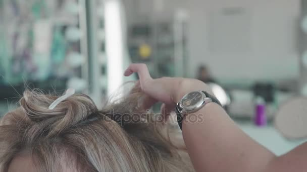 Close-up of a woman hairdresser making curls at blond hair