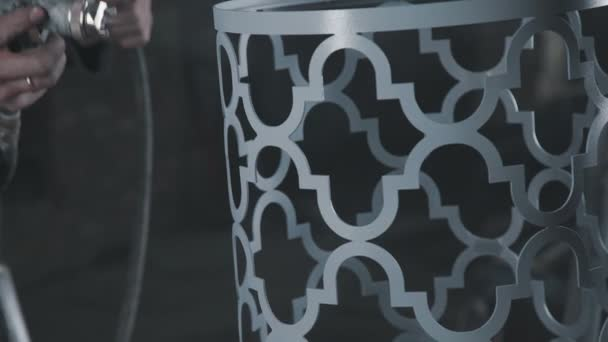 Decorative metal element of a cylindrical shape is painted by sprayer