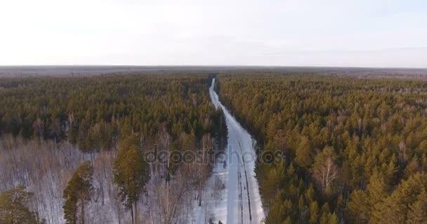 Nézd a helikopter a téli tűlevelű erdő és egy ország közúti
