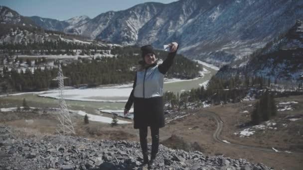 Nő egy ezüst kabát veszi selfie, háttérben a völgy