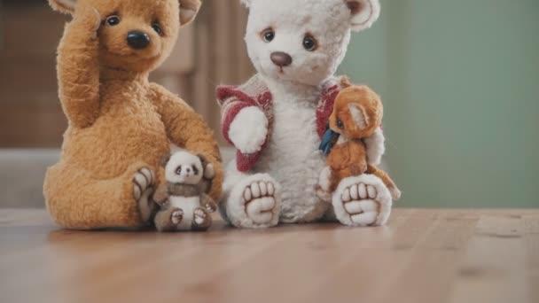 Plüss medvék kézzel: két nagy mackó és a két kis az asztalon