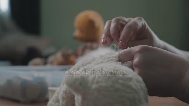 Jehly a podproces v rukou ženy - šije podrobnosti o plyšové hračky