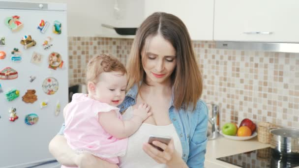 Young woman with baby and phone. Mother with baby and phone.