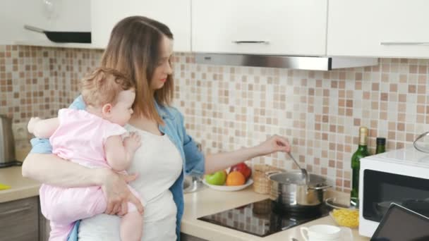 Mother holds little baby in arms and at the same time prepares food