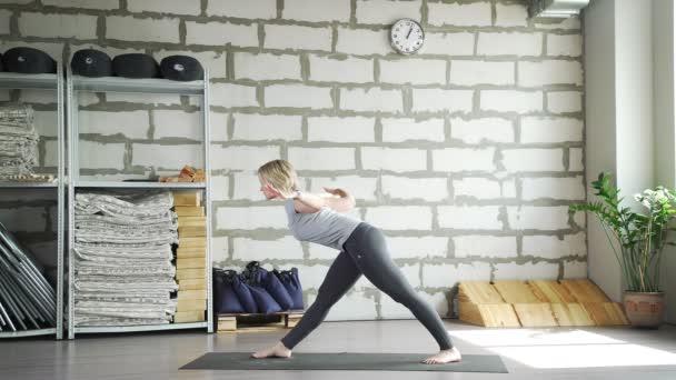 Žena dělá gymnastiku, využívá zařízení a umožňuje naklání doleva