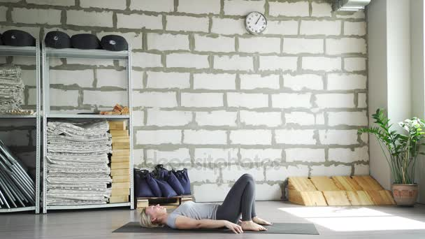 Zralá žena praxe jógy a dělá Ardha chakrasana