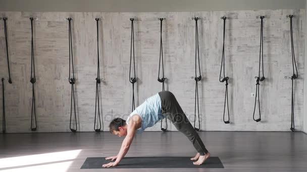 Samec yogin: muž v bílé tílko a šedé kalhoty cvičení jógy