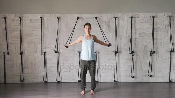 Muž v košili bez rukávů bílé tílko a šedé kalhoty dělá tělocvičnu