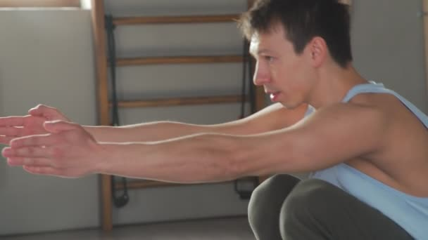Yogi muž provádí asana, takže hlubokého dřepu a vyvažování