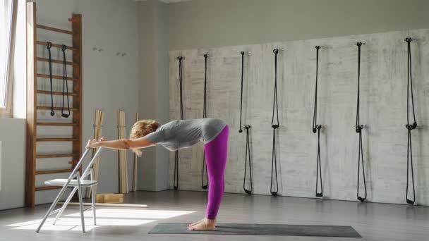 Zralá žena provádí jógu ásany, pomocí křeslo jako sportovní vybavení