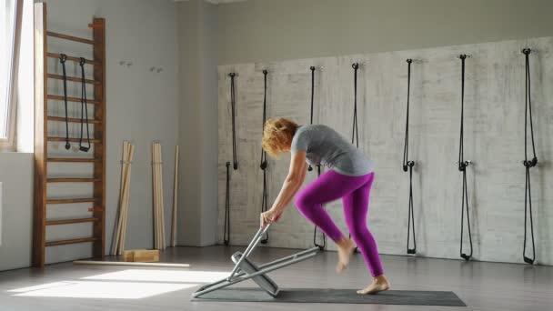 Školení pružnost a strečink: žena praxe jógy s židlí