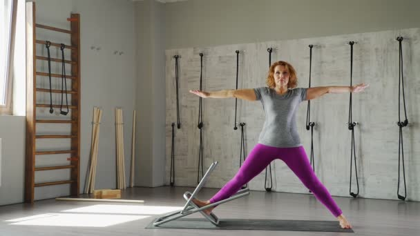 Zralá žena praxe jógy a provádí asana pózu bojovníka