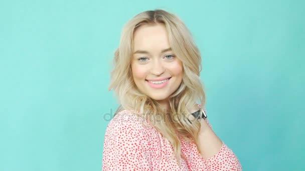 Finom szőke lány rózsaszín ruhát úgy néz ki, a kamera, és pózol.