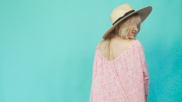 ein Mädchen mit Strohhut und Sommerkleid dreht sich um und zeigt ein Kleid.
