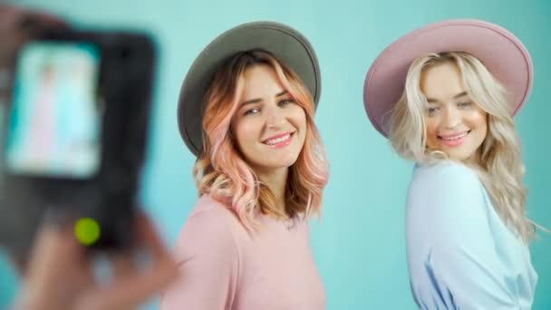 Zwei Modell-Mädchen sind für einen Fotografen in sanften Kleidern posieren.