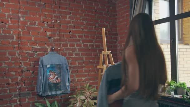 Tartist dokončení kreslení na džínové tkaniny, visí něco na zeď