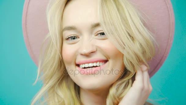 Krásný a něžný blondýna pózuje v růžovým klobouku, při pohledu do kamery