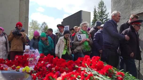 Rusko, Novosibirsk, 9. května 2017: lidé svalují květiny u Památníku