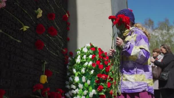 Rusko, Novosibirsk, 9. května 2017: dívka položit květiny k pomníku