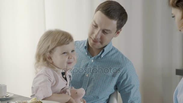 Az apák ölében ül egy kislány, anya játszik vele