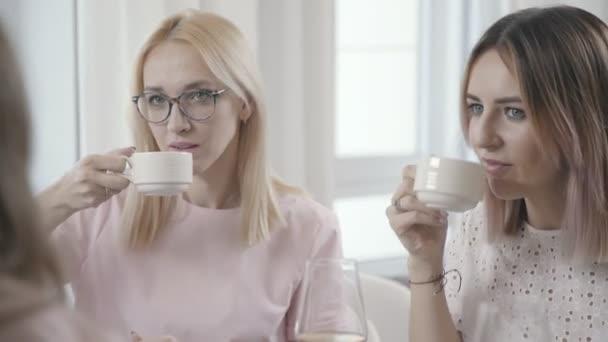 Two girls in restaurant drink tea and look at interlocutors opposite.