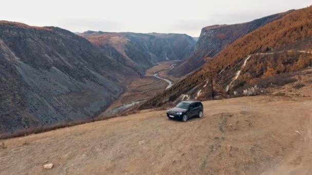 Velká černá crossover stojí na horské silnici, kolem - nikdo