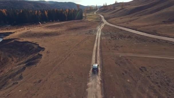 Velká černá crossover na projížďku po pouštní prašné horské silnici, po