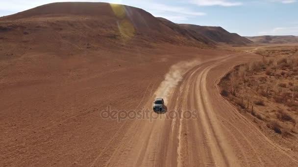 Autotravel: velké černé auto pohybuje vpřed přes písek road