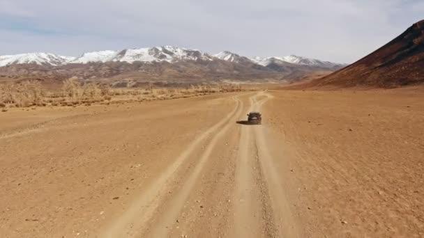 Černá crossover jezdí po pouštní prašné horské silnici terakota