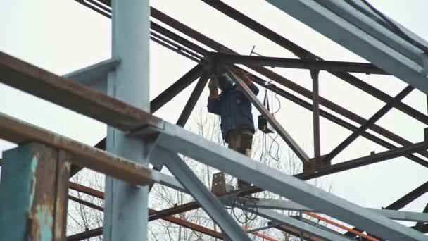 Stavební práce: kovový rám budovy. Svářeč v práci.