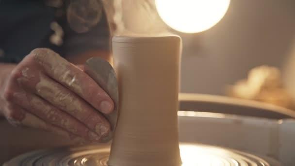 Potter hält ein spezielles Werkzeug und richtet die Oberfläche des zukünftigen Ton ware