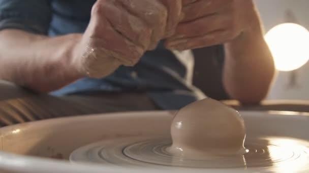 Mens Hände, gebeizt mit Lehm, arbeiten mit einer Töpferscheibe