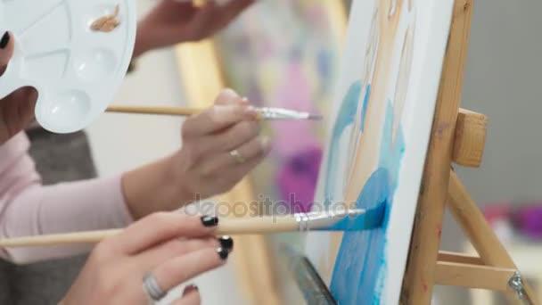 Umělec nakreslí barvy z palety pomocí štětce.