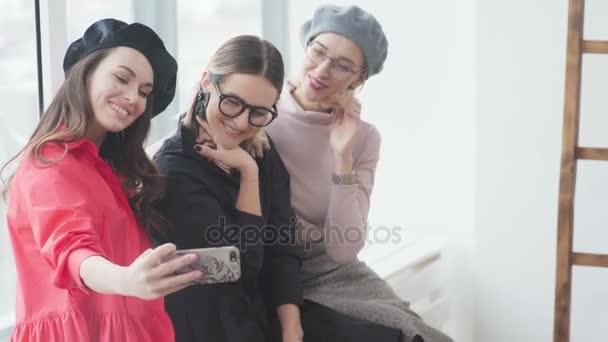 Tři mladí přátelé stylový trávit čas společně, vezměte selfie fotografie