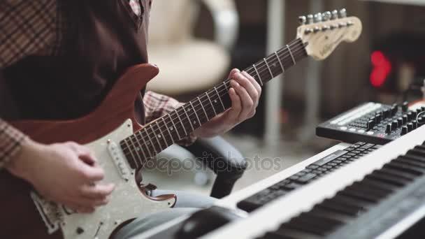 Elektrická kytara je v rukou hudebníka, detail. Vytváří stopy