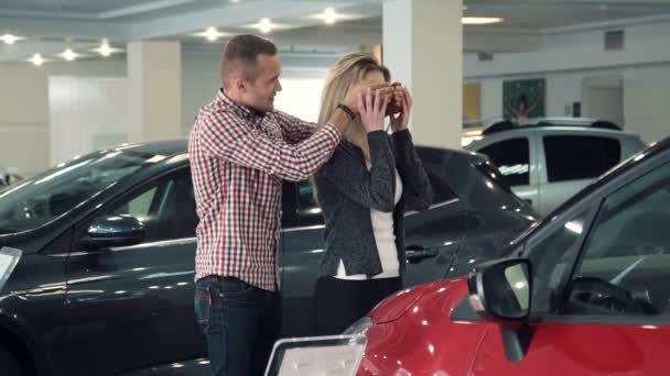 Slowmotion man surprises wife or girlfriend in car dealership, showing new car