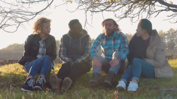 Four multiracial friends sitting at rural area.